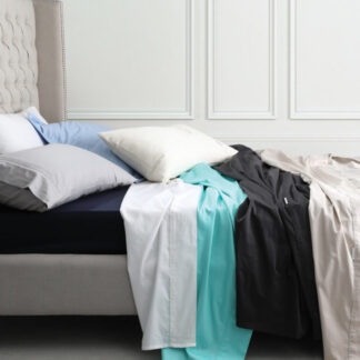 Egyptian Cotton Fitted Sheets in four different colours on a bed
