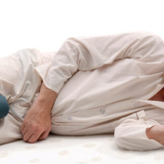 Older man using the Leg Spacer Cushion available online and in-store at The Back and Neck Bed Shop